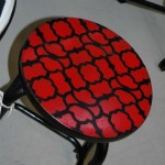 Black stool with red patterned seat